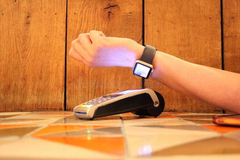 Contactless payment watch pdq with hand holding credit card to pay. Contactless payment watch pdq with hand holding credit card ready to pay nfc royalty free stock photography
