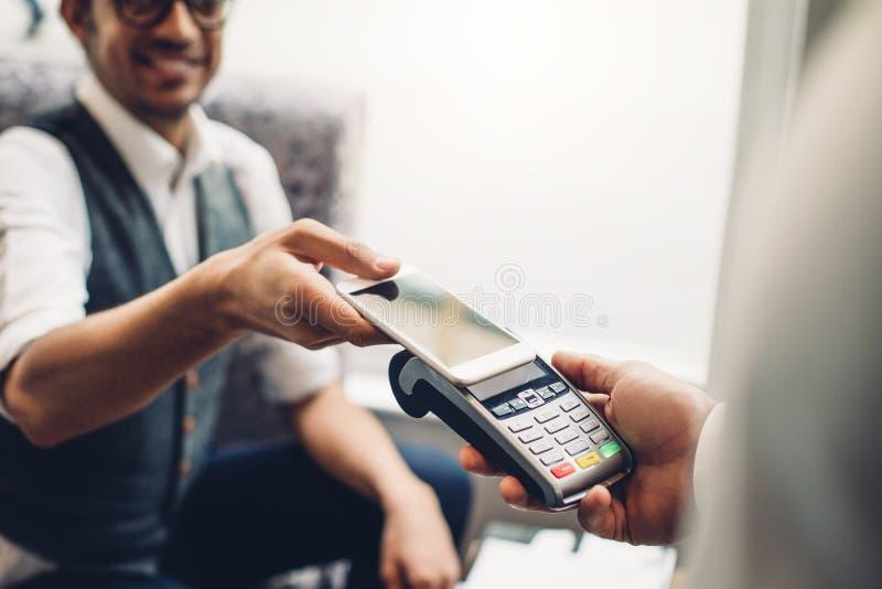 Contactless Smartphone Payment. Business men making a contactless smartphone payment royalty free stock photos