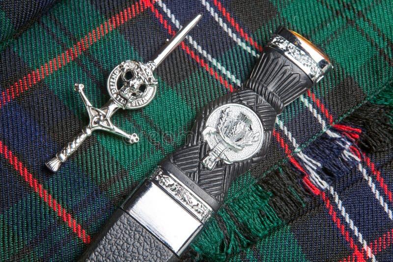 Contacto de la falda escocesa y cuchillo escocés imagenes de archivo