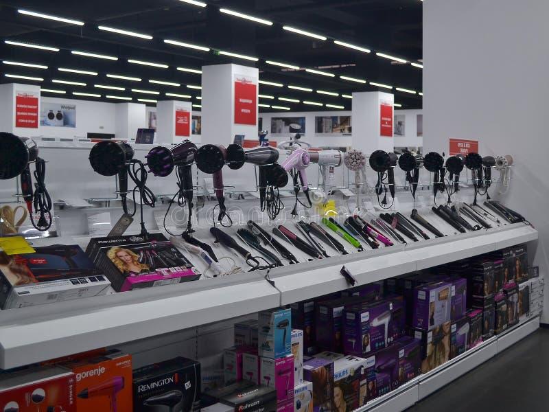 Contador com hairdryers e ferros de ondulação de fabricantes diferentes em uma loja de Technomarket em Varna fotografia de stock