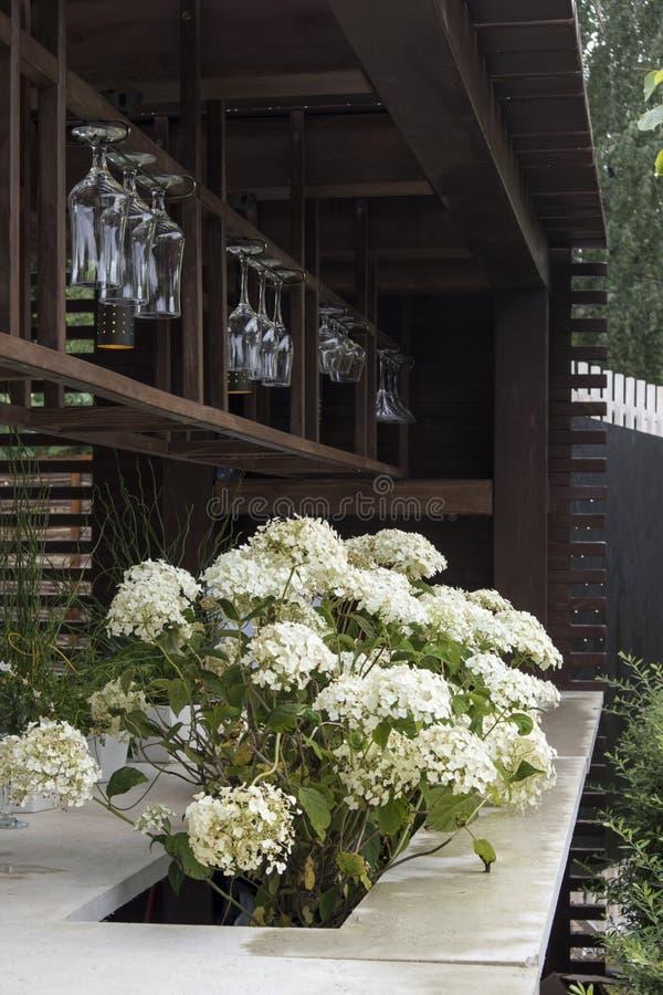 Contador da barra no jardim com vidros de vinho O Hortensia decora o jardim imagem de stock royalty free
