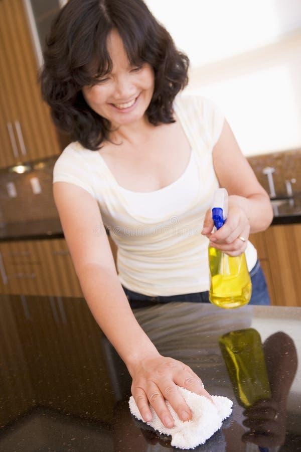 Contador de cocina de la limpieza de la mujer foto de archivo
