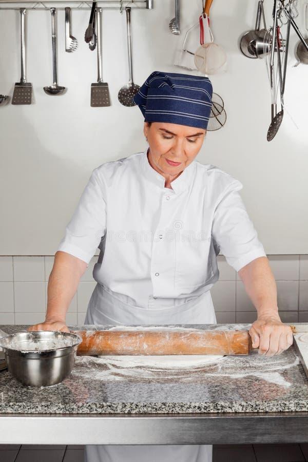 Contador de cozinha fêmea de Rolling Dough At do cozinheiro chefe foto de stock royalty free
