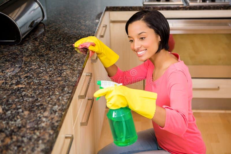 Contador de cozinha moreno de sorriso da limpeza fotografia de stock royalty free