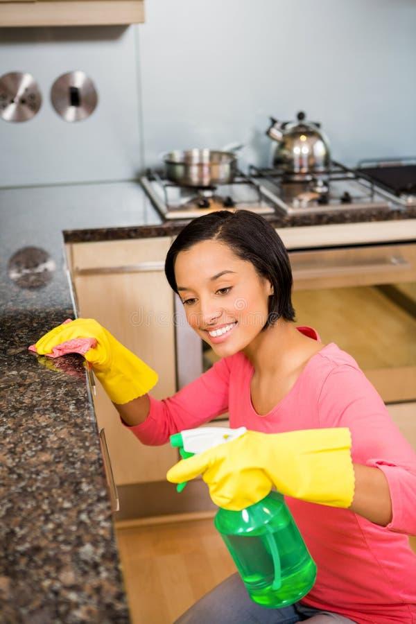 Contador de cozinha moreno de sorriso da limpeza imagem de stock royalty free