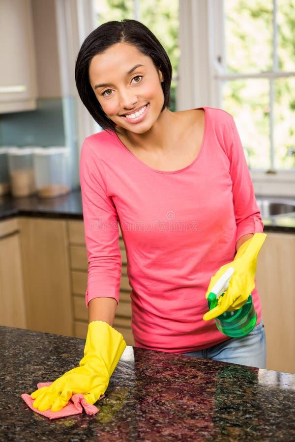 Contador de cozinha moreno de sorriso da limpeza fotos de stock