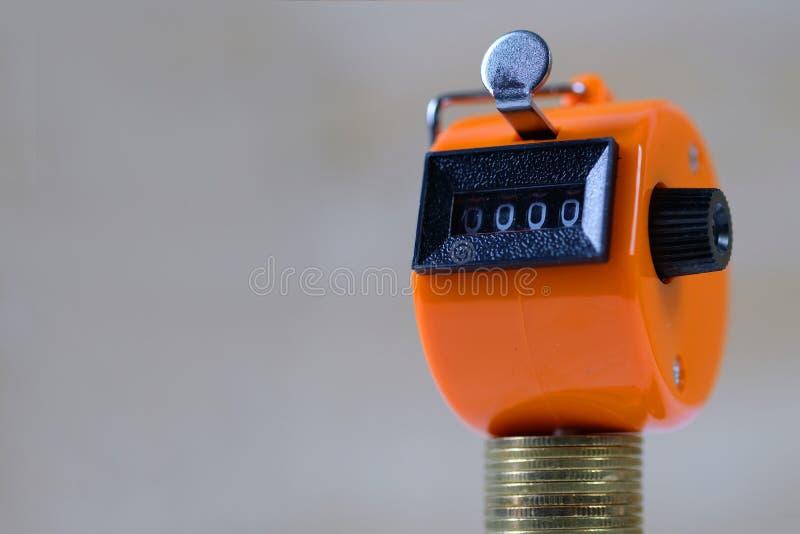 Contador de la cuenta o máquina de la cuenta con 0000 número, paso de la pila de la moneda en el concepto de madera blanco de la  fotografía de archivo libre de regalías