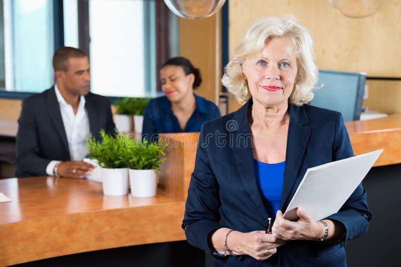 Contador de la recepción de Holding File At de la empresaria imagen de archivo