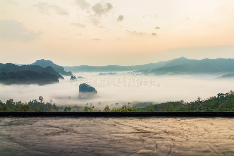 Contador de madera delante del paisaje de la montaña con el mar de la niebla foto de archivo