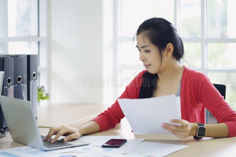 Contador de mulher que trabalha nas contas que planeiam o custo da renda de imposto na análise de negócio com relatório dos gráfi foto de stock