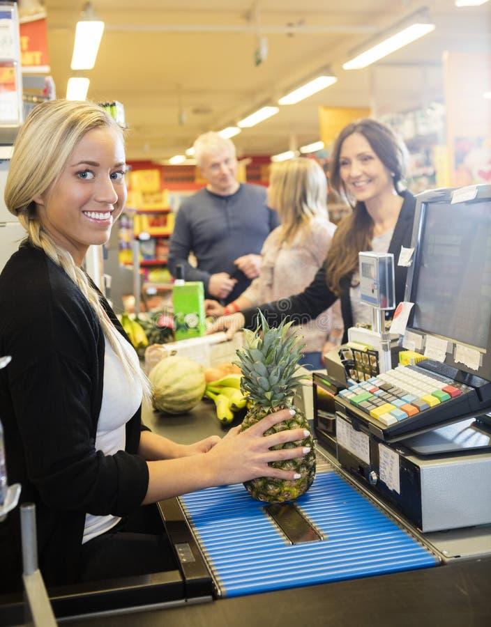 Contador de pago y envío confiado de Holding Pineapple At del cajero en estupendo imagen de archivo
