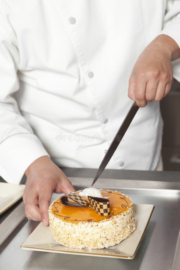 Contador de Slicing Cake At del cocinero en cocina comercial fotografía de archivo libre de regalías