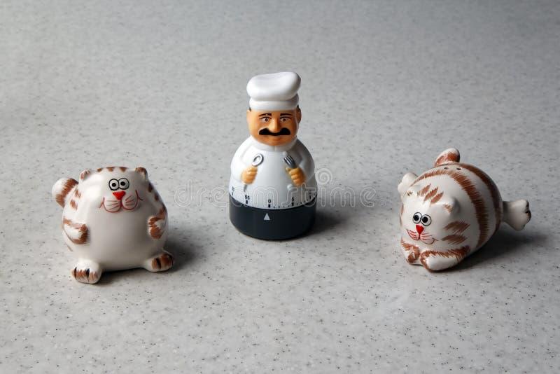 Contador de tiempo de la cocina bajo la forma de estatuilla del cocinero y dos gatos fotografía de archivo