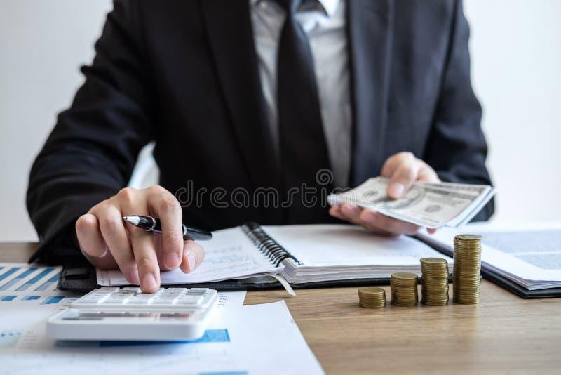 Contador do homem de negócios que conta o dinheiro e que faz anotações no relatório que faz finanças e para calcular sobre o cust imagens de stock