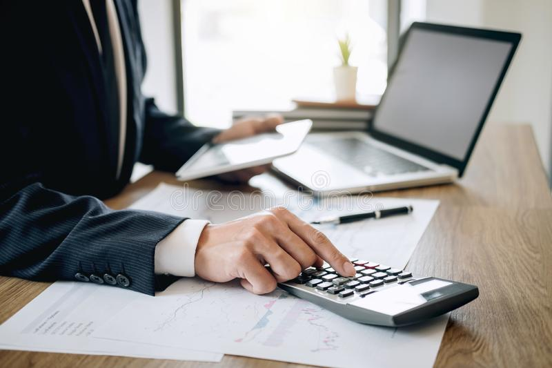 Contador do homem de negócios que trabalha o projeto novo no laptop com documento do relatório e para analisar o gráfico e o diag imagens de stock royalty free