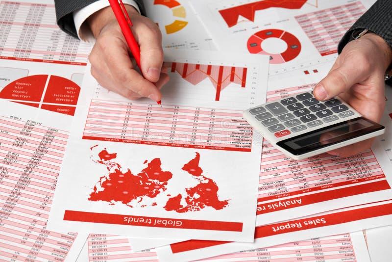 Contador do homem de negócios que usa a calculadora para calcular a finança no escritório da mesa Relatórios vermelhos do conceit fotografia de stock