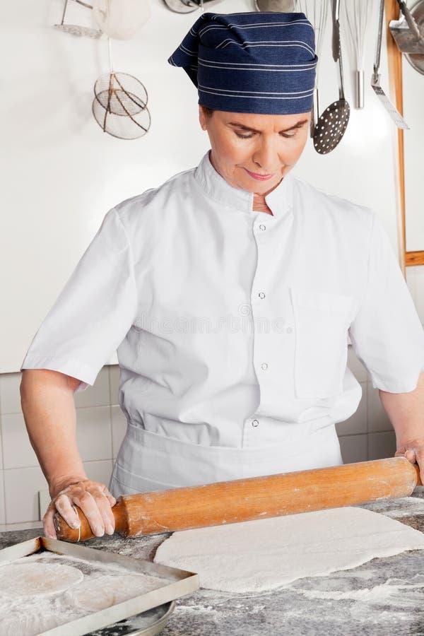 Contador fêmea de Rolling Dough On do cozinheiro chefe imagens de stock