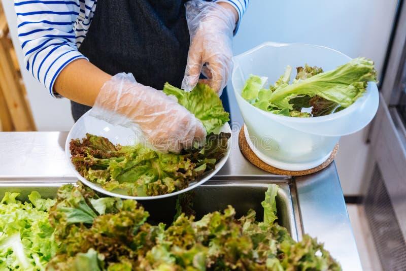 Contador fresco da barra de salada com as mãos da pessoa que levantam a alface em uma placa para a refeição saudável e da dieta c fotografia de stock