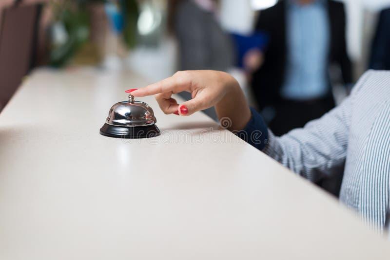 Contador moderno de la recepción del hotel de lujo de Bell de la prensa de la mano de la mujer de negocios fotografía de archivo