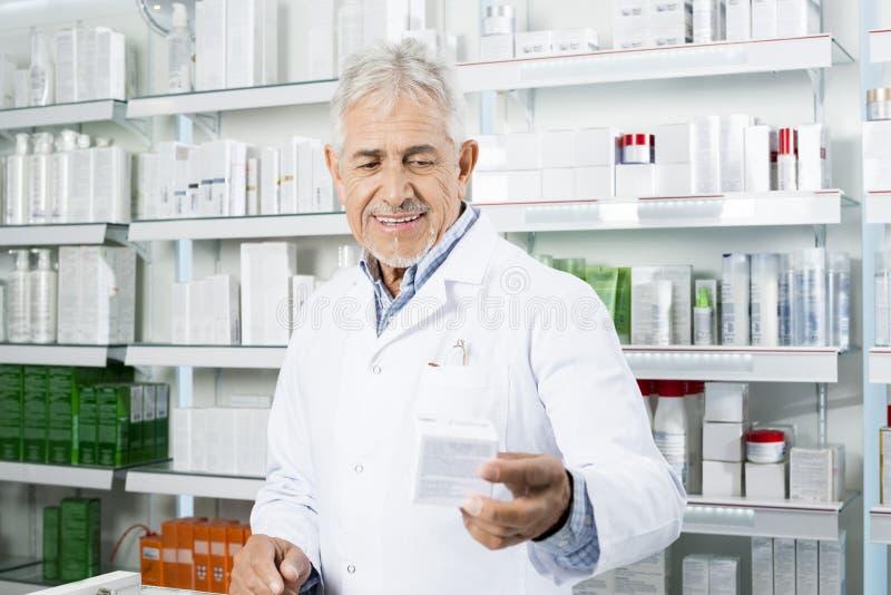 Contador sonriente de Holding Medicine At del químico en farmacia foto de archivo
