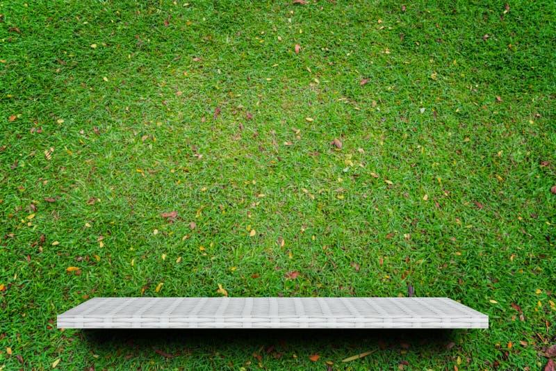 Contador vacío del estante en la hierba verde para la exhibición del producto imagenes de archivo