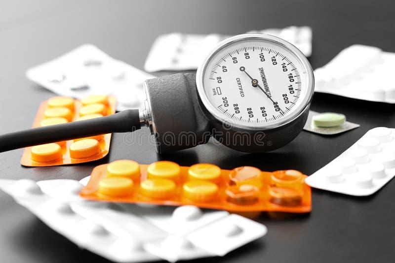 Contador y píldoras de la presión arterial en el vector imagenes de archivo