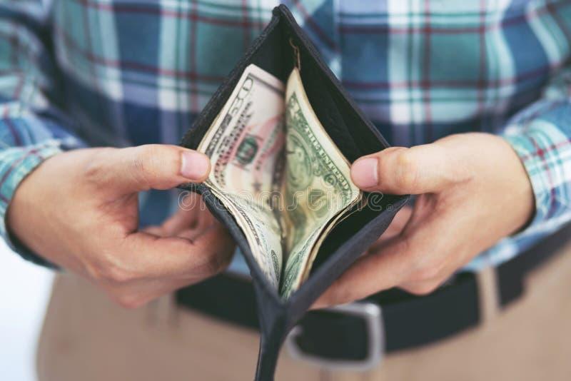Contagem ascendente próxima da posse da mão da posição do homem de negócio a propagação do dinheiro da carteira do dinheiro imagens de stock