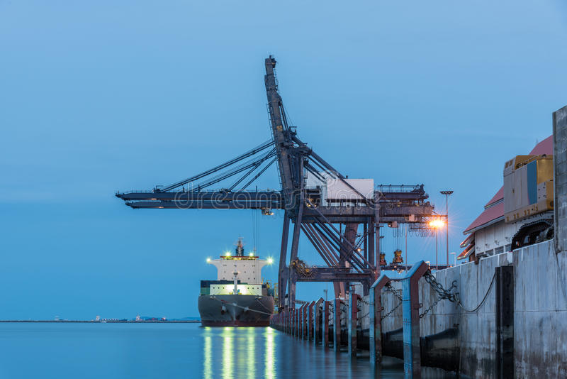 Container Cargo freight ship by crane bridge. Logistics harbor at sunrise stock photography