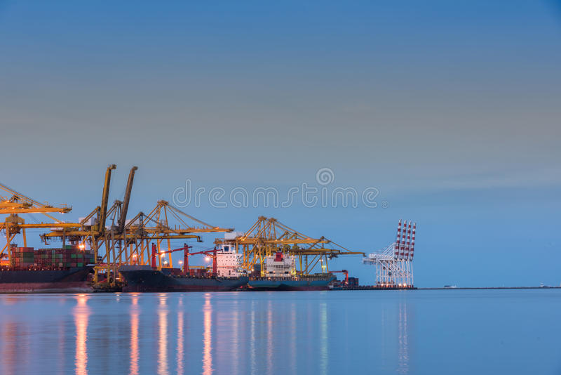 Container Cargo freight ship by crane bridge. Logistics harbor at sunrise royalty free stock photo