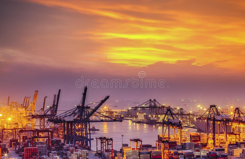 Container Cargo freight ship with working crane bridge in shipyard at dusk royalty free stock photo