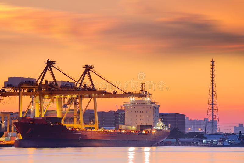 Container Cargo freight ship with working crane bridge in shipyard at dusk for Logistic Import Export background royalty free stock photography