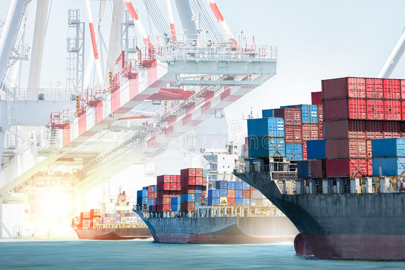 Container cargo ship entering the port with harbor crane background. stock images