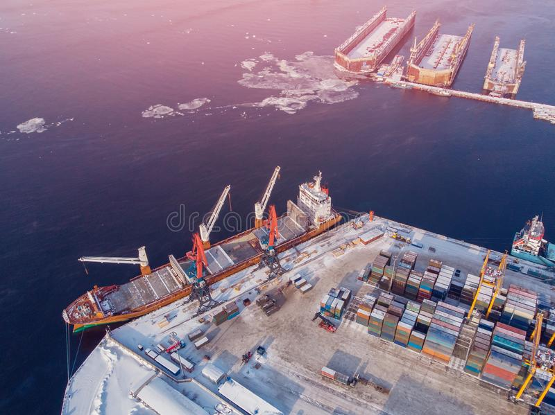 Container cargo ship loading North Arctic port. Concept freight transportation import export and business logistic. Aerial view winter stock photos