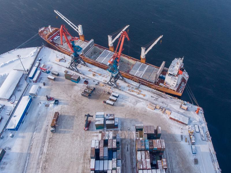 Container cargo ship loading North Arctic port. Concept freight transportation import export and business logistic. Aerial view winter royalty free stock image