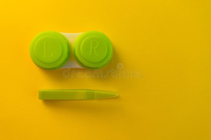 Green container for lenses on a yellow background royalty free stock image