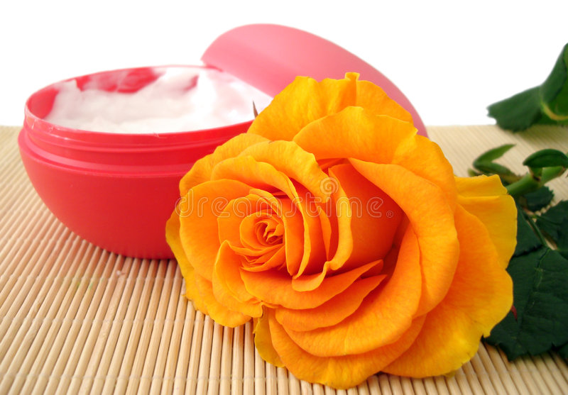 Container of cosmetic moisturizing cream with orange rose royalty free stock images