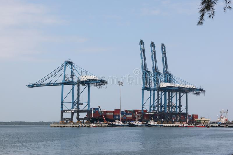 Container cranes at works, North Port, Port Klang, Malaysia. Port Klang, Malaysia - December 13, 2017 : Cranes unloading containers at Kelang Container Terminal stock images