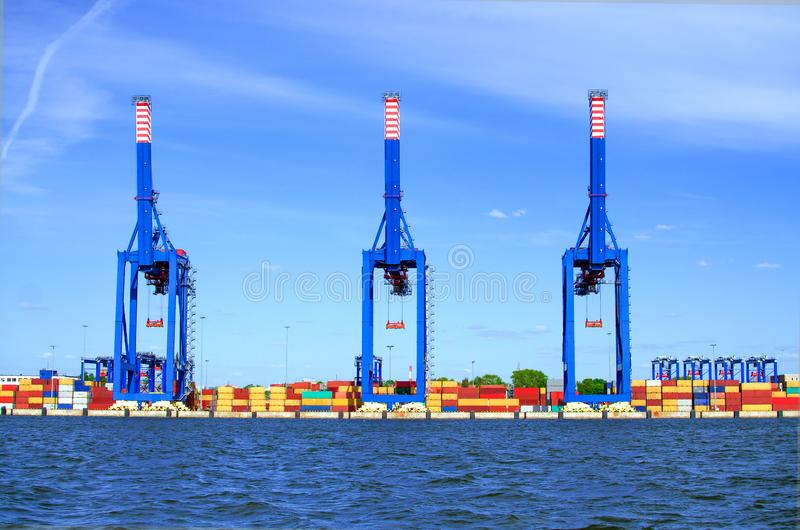 Shipping containers and cranes. New modern gantry crane in container terminal seaport stock images