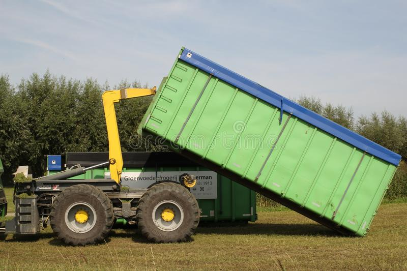 A container with grass seed is unloaded in the fields. A green container with grass seed is unloaded at the fields in zeeland, holland in summer royalty free stock image