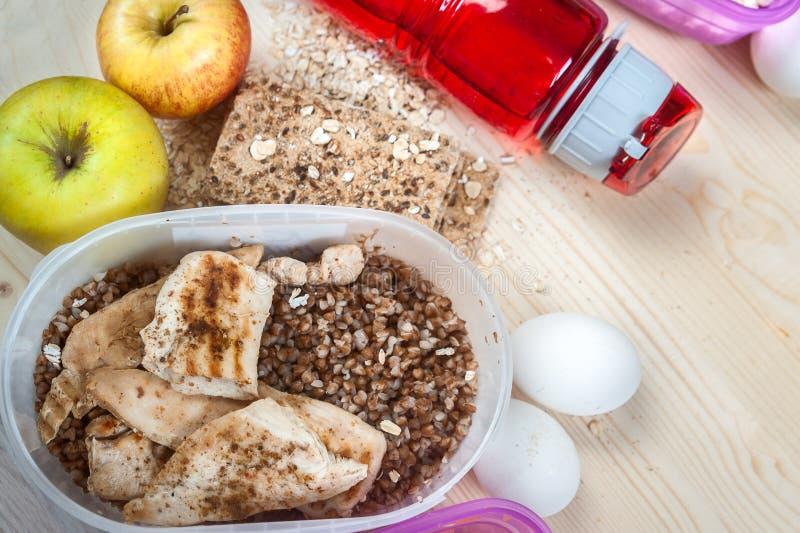 Container met boekweit en kip, appelen, brood, eieren Sportenvoeding royalty-vrije stock fotografie