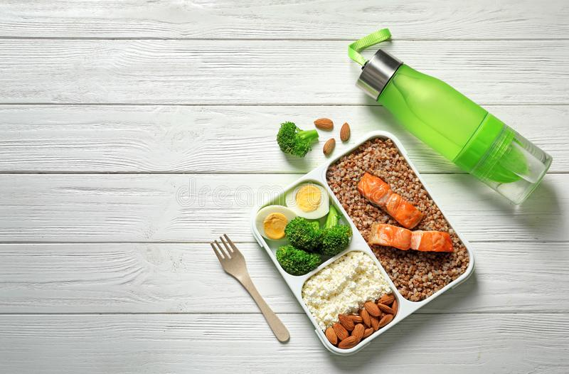 Container with natural healthy lunch, bottle of water and space for text on table, top view. High protein food royalty free stock photo