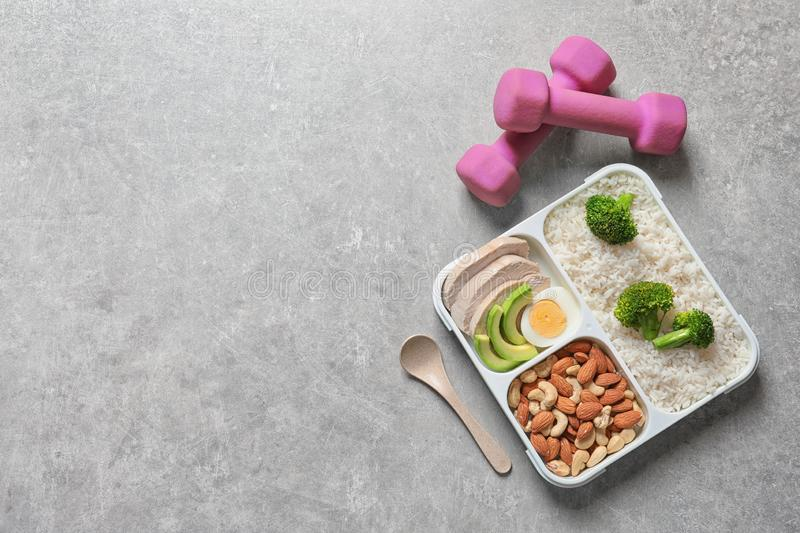 Container with natural healthy lunch, dumbbells and space for text on table, top view. royalty free stock images