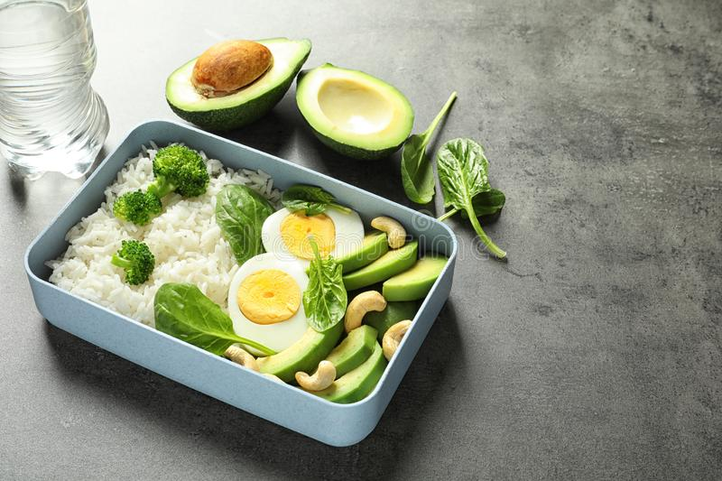 Container with natural healthy lunch on table, space for text stock images