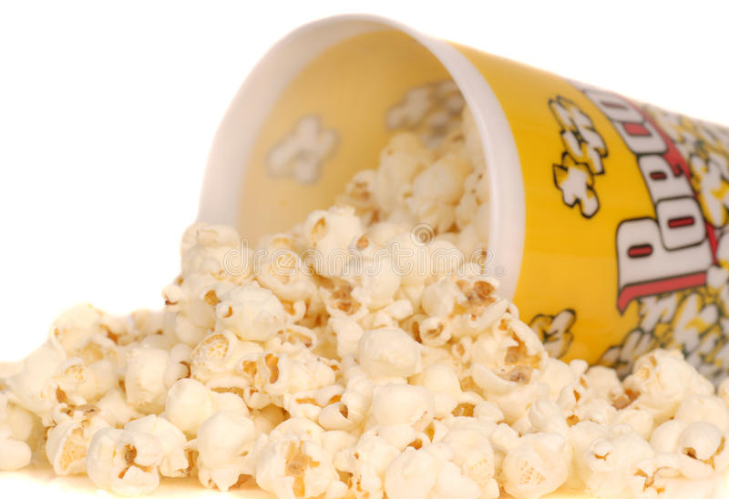 Container of popcorn with popcorn spilling out. Container of delicious movie popcorn with popcorn spilling out royalty free stock image