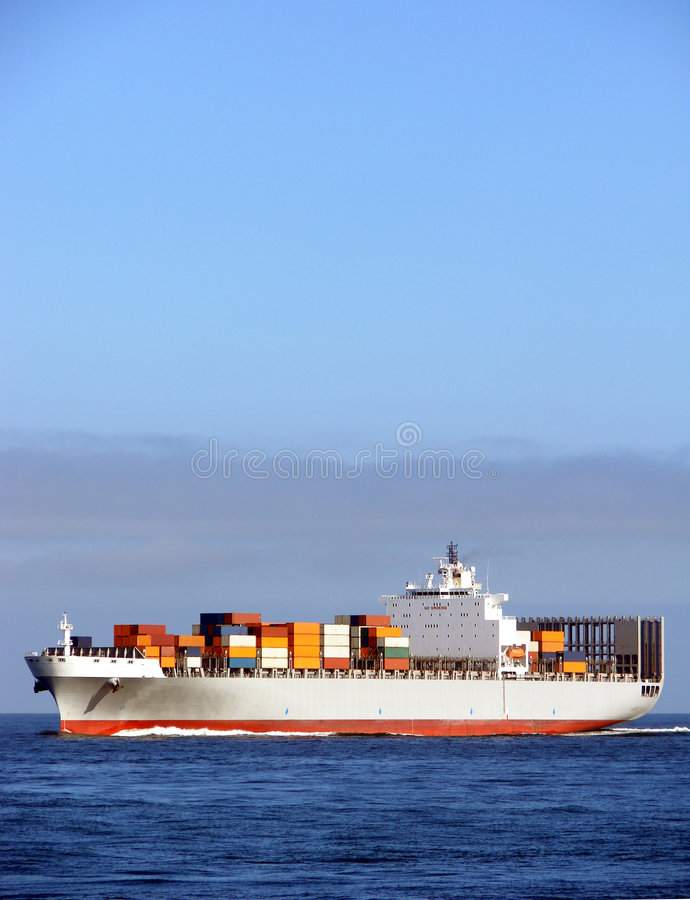 Container Ship with Deck Cargo Load Sailing at Sea. Ocean going container ship loaded with containers on deck sailing at sea royalty free stock images