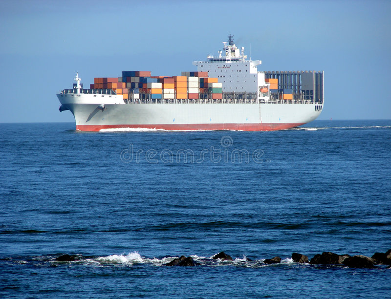 Container Ship with Deck Cargo Load Sailing at Sea. Loaded ocean going container ship with cargo on deck approaching rock bank at sea stock photography