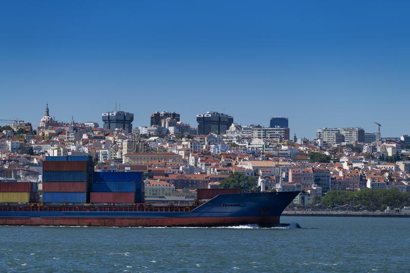 A container ship entering the port with the city of Lisbon skyline on the background royalty free stock photos