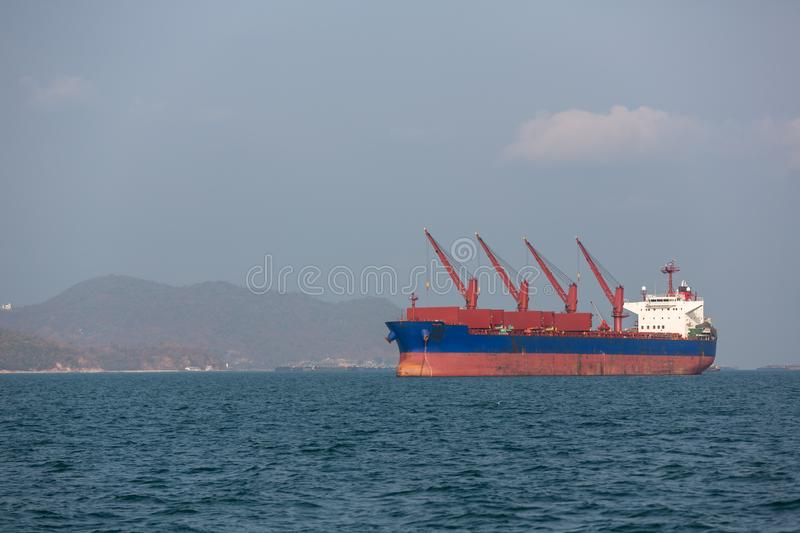 Container ship in export and import business and logistics. Shipping cargo to harbor by crane. Water transport International. Aerial view.Cargo ship carries royalty free stock image