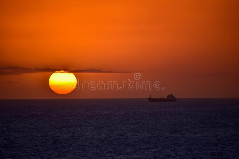 Container ship on the horizon at sunset stock images