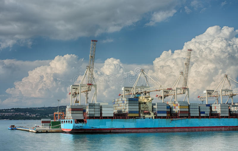 Container ship in industrial seaport of Koper in Slovenia. In a summer cloudy day stock image